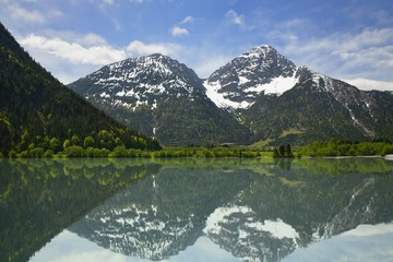 Reflection of snowy mountains on a lake at Alps
