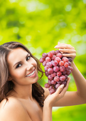 Young happy smiling woman with grapes, outdoors