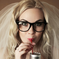 portrait of a funny beautiful hipster bride drinking soda