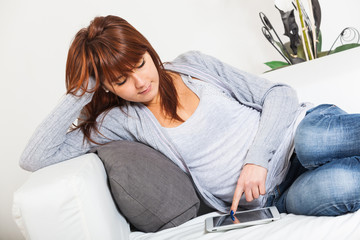 Beautiful Young Woman with Tablet PC on the Sofa