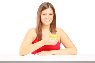 Young female holding a juice and posing on a table