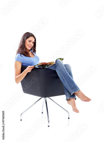 Casual 20s women sitting with magazine, looking to camera