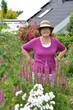 fröhliche Frau im sommerlichen Blumengarten