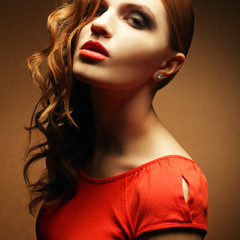 Portrait of an inaccessible beautiful ginger girl in orange dres