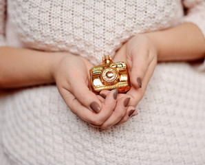 woman's hands with manicure holding a Christmas toy golden