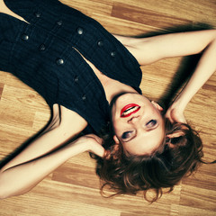 fashionable young woman lying on wooden floor and laughing. stud