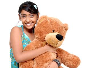 Pretty Indian girl embracing teddy bear