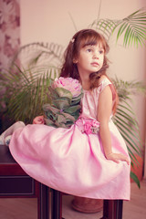 little girl model view in a luxury pink dress and flower posing
