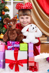 Beautiful little girl in red dress surrounded by gifts and toys