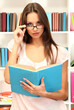 Young attractive female student reads book in library