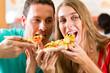 Mann und Frau essen eine Pizza