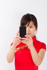 Cheongsam Asian woman, with mobile phone in photographs