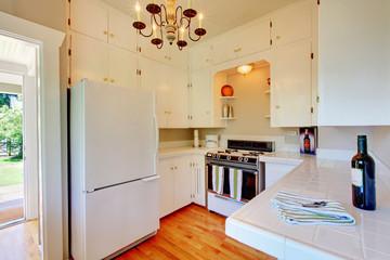 White kitchen with hardwood floor and open door.