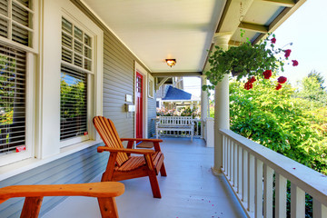Front porch of the grey house with white railings