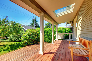 Large covered porch with skylight and wood bench and floor.