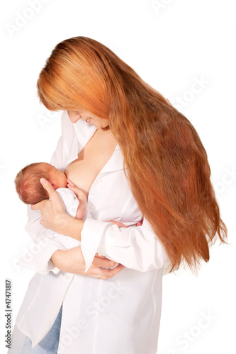 The red-haired mother breastfeeding newborn baby.