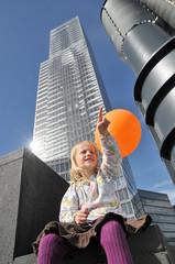 Kleines Mädchen mit Ballon vor Hochhaus
