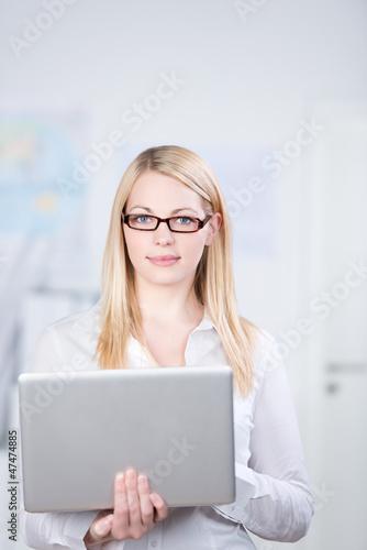 lächelnde frau im büro mit laptop
