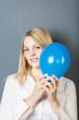 portrait frau mit luftballon vor grauer wand