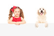 A small girl and Labrador retriever posing behind a panel