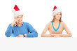 Smiling couple wearing santa hats and posing behind a panel