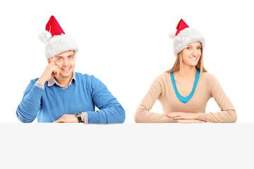 Smiling couple wearing santa hats and posing behind a panel