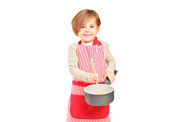 Smiling small girl holding a frying pan and kitchen utensil