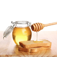 Honey with stick pouring over toast bread