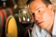 Mann testet Wein im Hintergrund Weinfässer