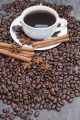 Coffee with cinnamon sticks and star anise surrounded by beans