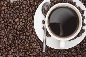 Steaming hot cup of coffee  surrounded by dark coffee beans with