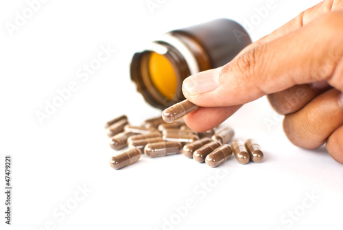 Hand putting medicine isolated on the white.