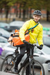Male Cyclist With Courier Delivery Bag On Street