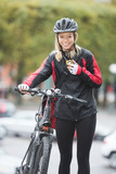Female Cyclist With Courier Bag Using Walkie-Talkie