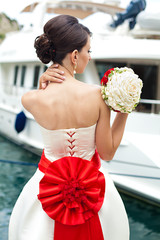 bride with beautiful bouquet and hair gathered near the boat
