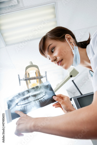 Female Dentist Looking At X-Ray Image