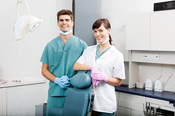 Two Dentists Smiling By Dental Chair At Clinic