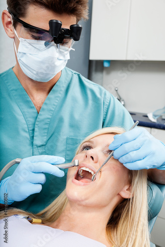 Dentist Treating A Female Patient At Clinic