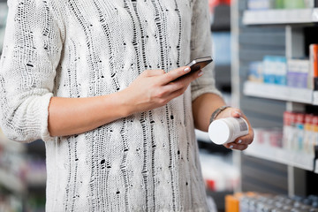 Woman Scanning Bottle with Smar Phone