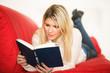 Blondine mit Buch auf der Couch
