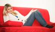 Blondine telefoniert auf dem Sofa
