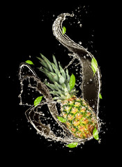 Pine-apple in water splash, isolated on black background