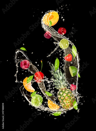 Fresh fruits falling in water splash on black background