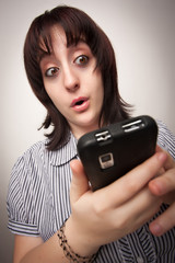 Stunned Brunette Woman Using Cell Phone