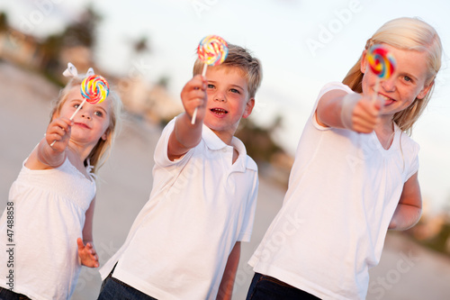 Cute Brother and Sisters Enjoying Their Lollipops Outside