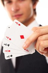 Handsome young man holding playing cards