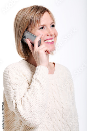 Caucasian middle aged woman talking by cellphone smiling