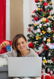 Woman with laptop and credit card sitting near Christmas tree