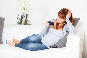 Beautiful Young Woman with Smartphone on the Sofa