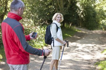 A mature couple walking, navigating with a smartphone